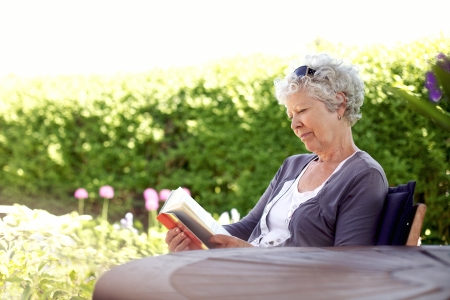 Senior woman reading a book sitting outside on a chair at the garden. Elder woman reading novel at her backward garden photo