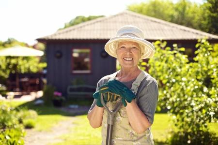 Portret van vrolijke senior vrouw met tuingereedschap buitenshuis. Oudere vrouw met schop in haar achtertuin tuin Stockfoto
