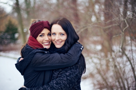 Friends hugging each other on a bright winter day with white snow on background photo