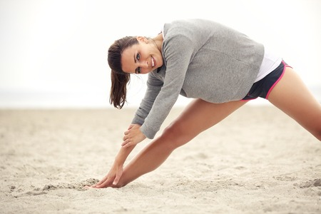 Outdoor female athlete doing her morning stretching and yoga exercise on the beach while smiling and looking happy. photo
