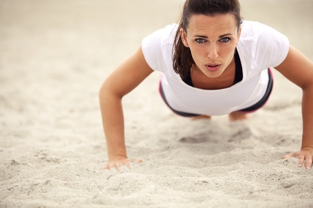 Push-ups fitness woman doing pushups outside on beach. Fit female sport model girl training crossfit outdoors. Caucasian athlete in her 20s. photo