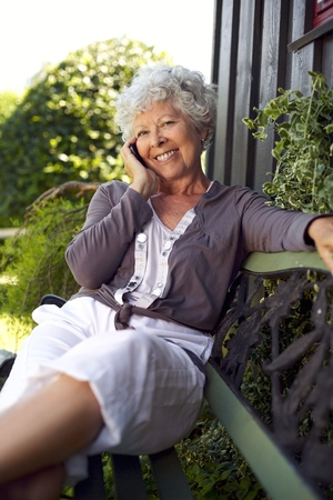 Happy senior woman sitting on a bench in backyard talking on mobile phone and smiling photo