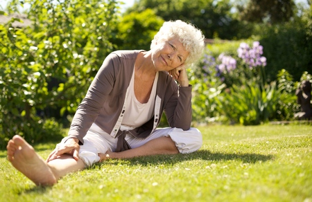 Mature woman sitting down on grass comfortably in garden looking at you - Outdoors photo