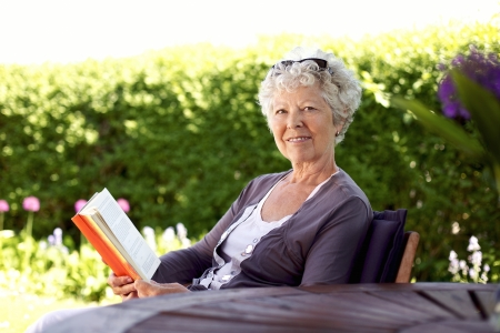 Happy senior woman with book in hand sitting in her backyard looking at camera smiling - Elder woman reading novel in garden photo
