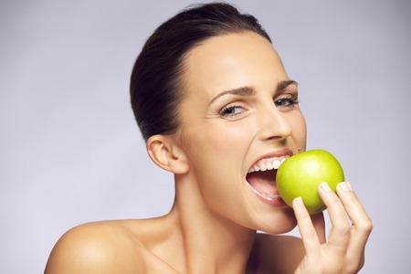 Closeup portrait of lovely young brunette woman biting juicy fresh delicious apple against gray background. Beautiful young lady eating healthy food. photo
