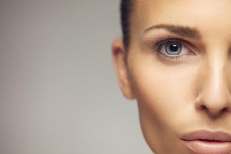 완벽하게 건강한 피부와 아름 다운 눈을 가진 예쁜 젊은 여자의 초상화를 확대합니다. 회색 배경에 꽤 젊은 여성의 절반 얼굴