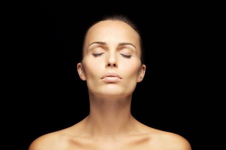 mujeres negras desnudas: Hermosa mujer morena con los ojos cerrados sobre fondo negro. Hermosa joven soñando en el fondo negro Foto de archivo