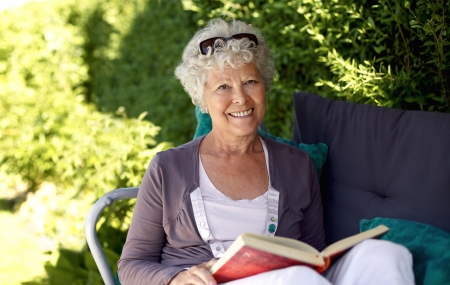 Elder woman sitting on a chair in backyard garden holding a book and looking at camera smiling photo