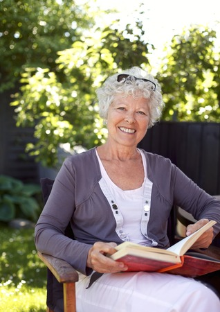 Elderly woman relaxing on a chair in garden with a book looking at camera smiling - Senior woman reading outdoors photo