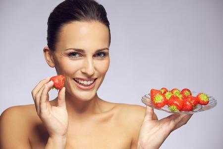 Portrait of beautiful and lovely young woman with a plate of fresh strawberries photo
