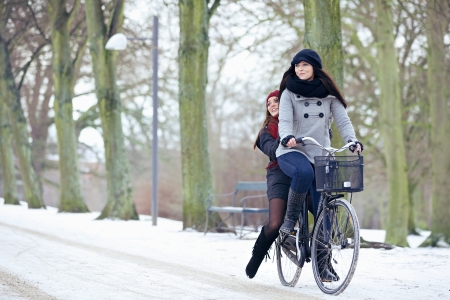 Happy women enjoying a bike ride in a winter park photo