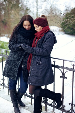 girl boots: Two young women at winter park looking at something with white snow at the background