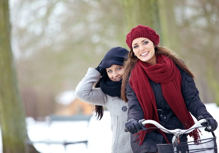 Two friends enjoying their winter vacation outdoors riding a bike photo