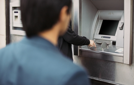 criminal activity: Man withdrawing cash at an ATM with a thief following him Stock Photo