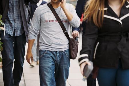 彼が携帯電話で話している間、男性のハンドバッグから財布を盗んだ泥棒。昼間の間に通りでのスリ 写真素材 - 22996461