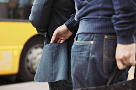 pickpocket: Thief stealing wallet of a man walking on the street. Pickpocketing on the street during daytime Stock Photo
