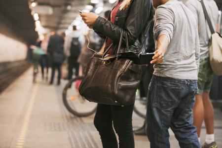 ladrones: Ladr�n roba la cartera del bolso de una mujer utilizando tel�fono m�vil en la estaci�n de metro. Los carteristas en la estaci�n de metro Foto de archivo