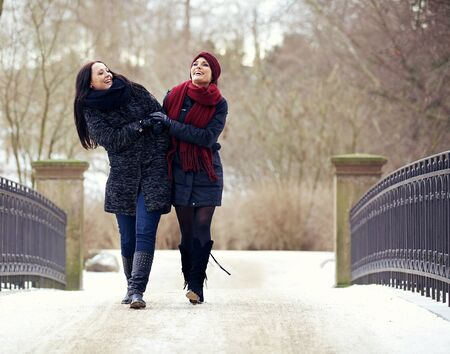 Two cheerful friends enjoying strolling in the cold winter park photo