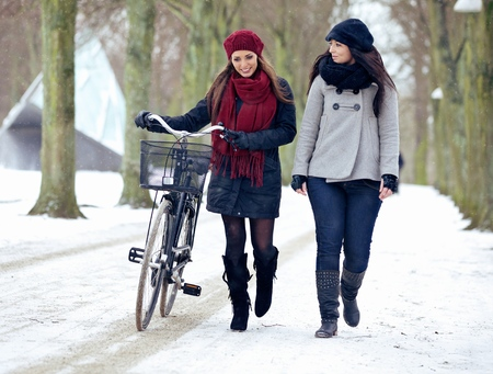 Two friends enjoying their walk on a cold winter outdoors photo