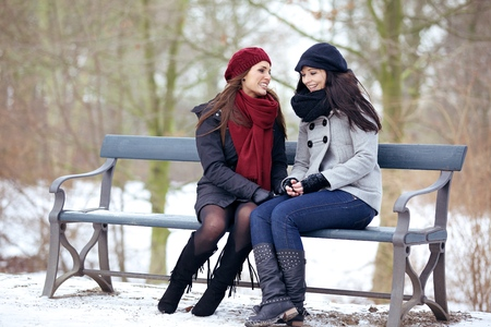 amigas conversando: Dos bestfriends sentado en un banco del parque y tener una conversación divertida