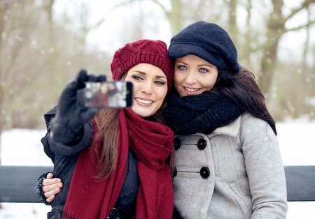 Outdoor women taking pictures  using a smartphone photo