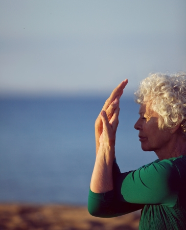 Old woman stretching her arms by the sea. Senior caucasian woman exercising on beach in morning. Fitness and healthy lifestyle concept. photo