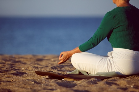 Cropped image of senior woman in meditation on sandy beach. Elderly woman sitting on the beach in lotus pose doing relaxation exercise . Mature woman doing yoga photo