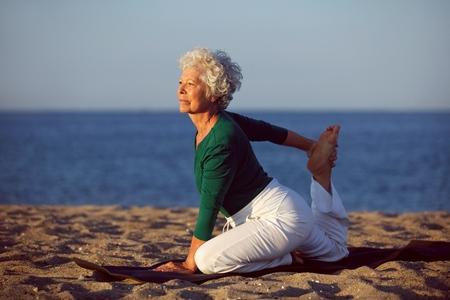 persona mayor: Superior de la mujer en posición de estiramiento por el mar en la mañana. Mujer mayor que hace yoga en la playa.