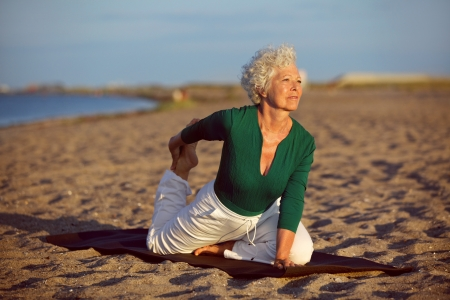 senior yoga: Senior woman in stretching position by the sea at morning. Elderly woman doing yoga on the beach.