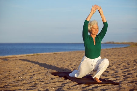 Senior woman practicing yoga poses on the sandy beach. Elder caucasian woman stretching legs and arms on the seashore. Healthy lifestyle and fitness concept photo