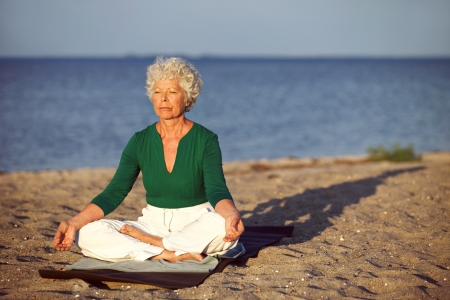 beach mat: Elderly woman sitting on exercise mat doing meditation in lotus pose on the beach. Old woman doing relaxation exercise on the seashore. Meditation, yoga and relaxation concept Stock Photo