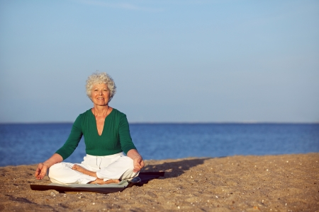 Portrait of the senior woman meditating on the seashore with lots of copyspace. Elder woman doing relaxation exercise on sandy beach during morning. photo