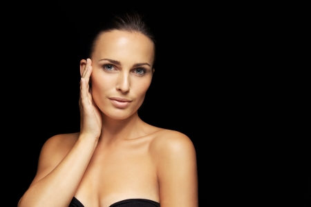 touching face: Happy pretty young woman model with beautiful skin. Lovely female holding hand by her face touching her healthy skin. Attractive young woman against black