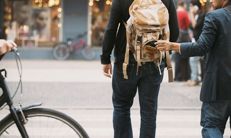 stealing: Thief stealing wallet from backpack of a man walking on street during daytime.  Pickpocketing on the street during daytime Stock Photo
