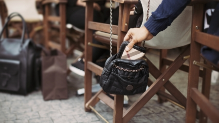 pickpocket: Man taking wallet out of a womans purse at street cafe during daytime. Thief stealing purse. Pickpocketing at the street cafe Stock Photo