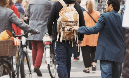 thievery: Young man taking wallet from backpack of a man walking on street during daytime. Pickpocketing on the street during daytime