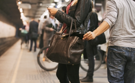 ladrones: Mujer joven que usa el tel�fono m�vil siendo robado por un carterista en la estaci�n de metro. Los carteristas en la estaci�n de metro