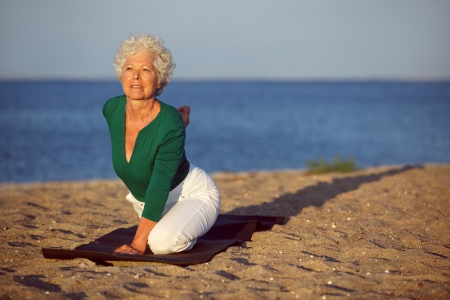 Mature caucasian woman in stretching position at beach. Senior woman doing yoga by the sea in morning photo