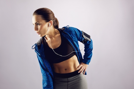 Attractive young fitness woman listening to music and looking away on grey . Female wearing sportswear and earphones looking at copyspace. photo