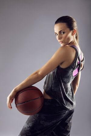 Portrait of young female basketball player looking over shoulder at camera against grey  photo