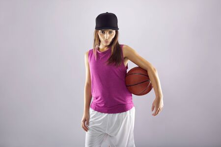 Confident young woman holding basketball. Beautiful caucasian female basketball player on grey  photo