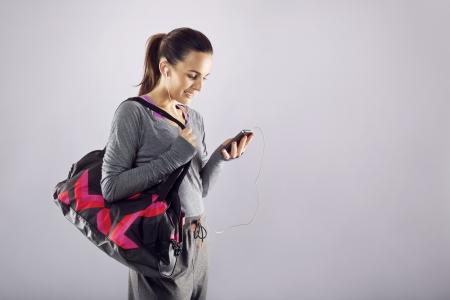스포츠 가방이 그녀의 휴대 전화에 음악을 듣고 좋은 찾고 여성 선수. 회색에 헬스 클럽에가는 스포츠 의류에 피트 니스 여자 스톡 콘텐츠