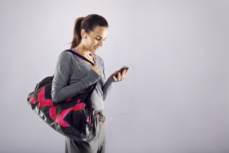 Good looking female athlete with a sports bag listening to music on her mobile phone. Fitness woman in sports clothing going to gym on grey  photo