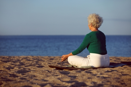 Side view of elderly woman in meditation on the beach. Senior lady sitting on the beach in lotus pose doing relaxation exercise. Old woman doing yoga.