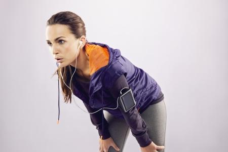 deportista: Cansado de la mujer atleta caucásico inclinándose después de correr. Mujer joven en ropa deportiva relajarse después de un trote en gris