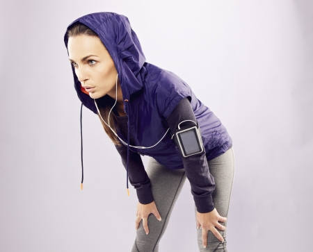 Young caucasian woman taking breath after jogging. Female athlete resting with hands on knees and looking away over grey background photo