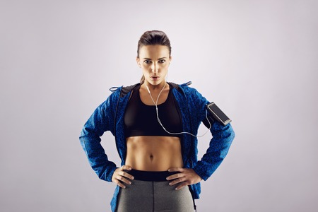 hands on hips: Attractive young woman in sportswear poses for the camera with her hands on her hips. Determined female athlete looking at camera while standing against grey  Stock Photo