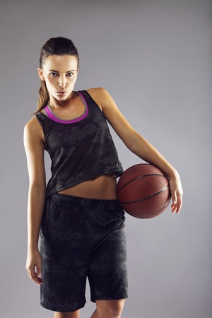 Portrait of beautiful young female basketball player in uniform with a basketball posing on grey  photo