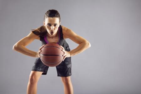 baloncesto chica: Retrato del jugador de b�squet de sexo femenino joven que pasa la pelota. Hermosa mujer cauc�sica en ropa deportiva de baloncesto que juega en gris con copyspace
