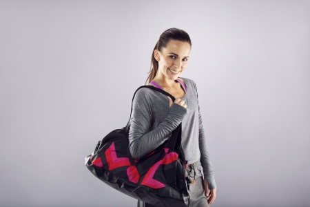 Happy fit young woman with gym bag standing ready for fitness exercise. Young caucasian female going for gym looking at camera smiling. Representing a healthy lifestyle. photo